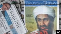 A roadside vendor sells newspapers with headlines about the death of al-Qaida leader Osama bin Laden in Lahore, Pakistan, May 3, 2011.