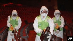 Workers wearing protective gears, spray antiseptic solution as a precaution against the spread of MERS, Middle East Respiratory Syndrome, virus at the Sejong Culture Center in Seoul, South Korea, Tuesday, June 16, 2015.