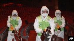 Công nhân mặc đồ bảo hộ, phun dung dịch sát khuẩn để phòng chống sự lây lan của MERS tại Trung tâm Văn hóa Sejong ở Seoul, Hàn Quốc.