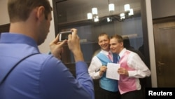 Mark Massey (C) and Dale Frost (R) pose for a picture after registering their marriage at the City Clerk's Office in New York, October 11, 2012.