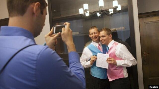 Anh Mark Massey (ở giữa) và anh Dale Frost (phải) cùng chụp ảnh sau khi đăng kí kết hôn tại New York, 11/10/2012. (REUTERS/Andrew Kelly)