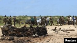 Jubaland forces and Somali residents stand near the site of a suicide car bomb attack near a military training base in the port town Kismayu, south of Mogadishu, Aug. 22, 2015.