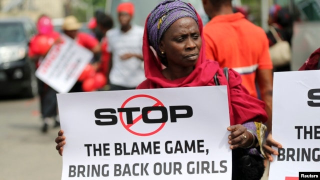 A woman carries a sign as she attends a protest demanding the release of abducted secondary school girls in the remote village of Chibok, in Lagos May 9, 2014.