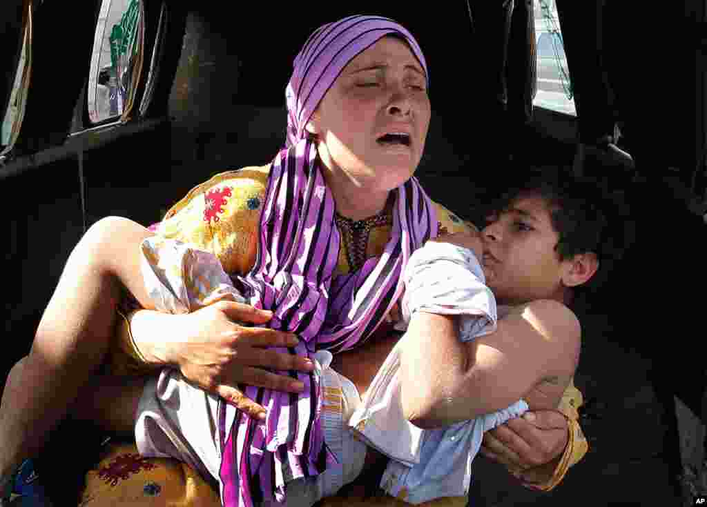 May 30: A Syrian woman cries as she carries her son who was shot in the hand by a Syrian border guard when they were crossing a river from Syria to Lebanon, at the northern border town of Wadi Khaled, north Lebanon.