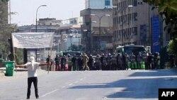 Một người biểu tình phản đối ở Khalidia, gần Homs đứng đối mặt với cảnh sát chống bạo loạn hôm 4/11/11