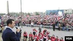 Presiden Suriah, Bashar al-Assad, berpidato di hadapan ribuan pendukungnya yang mengadaikan pawai di lapangan Umayyad, Damaskus (11/1).