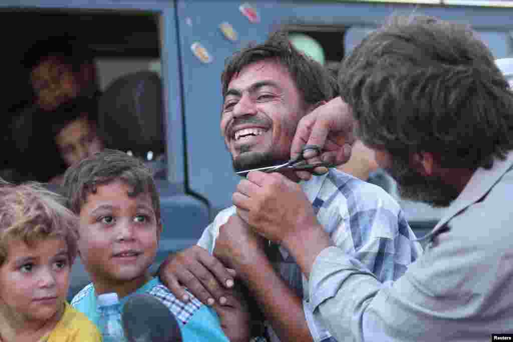 Seorang pria memotong janggut seorang warga sipil yang dievakuasi bersama yang lainnya oleh Pasukan Demokratis Suriah (SDF) dari kota Manbij yang dikuasai ISIS di Aleppo, Suriah (12/8). (Reuters/Rodi Said)