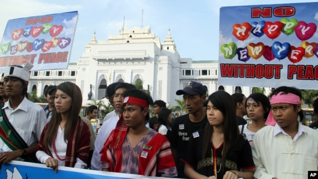 Clad in traditional attire, activists march during a rally to end the fighting in northern Burma, in downtown Rangoon, Tuesday, January 1, 2013.