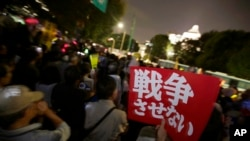 "A sign that reads: ""We won't let Japan go to war"" is held by a protester as people gather for an anti-war rally in front of the National Diet building in Tokyo, Tuesday, Sept. 15, 2015."