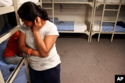 FILE - A Guatemalan woman stands inside a dormitory in a federal detention facility for undocumented immigrant mothers and children in Artesia, New Mexico, Sept. 10, 2014.