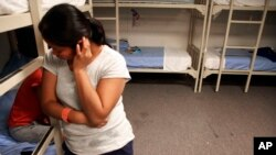 FILE - A Guatemalan woman stands inside a dormitory in a federal detention facility for undocumented immigrant mothers and children in Artesia, N.M., Sept. 10, 2014. The nation's immigration courts are facing a backlog of more than half a million cases.