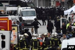 Firefighters and police are gathered in the northern Paris suburb of Saint-Denis on Nov. 18, 2015, as special forces raid an appartment, hunting those behind the attacks that killed 129 in the French capital last week.