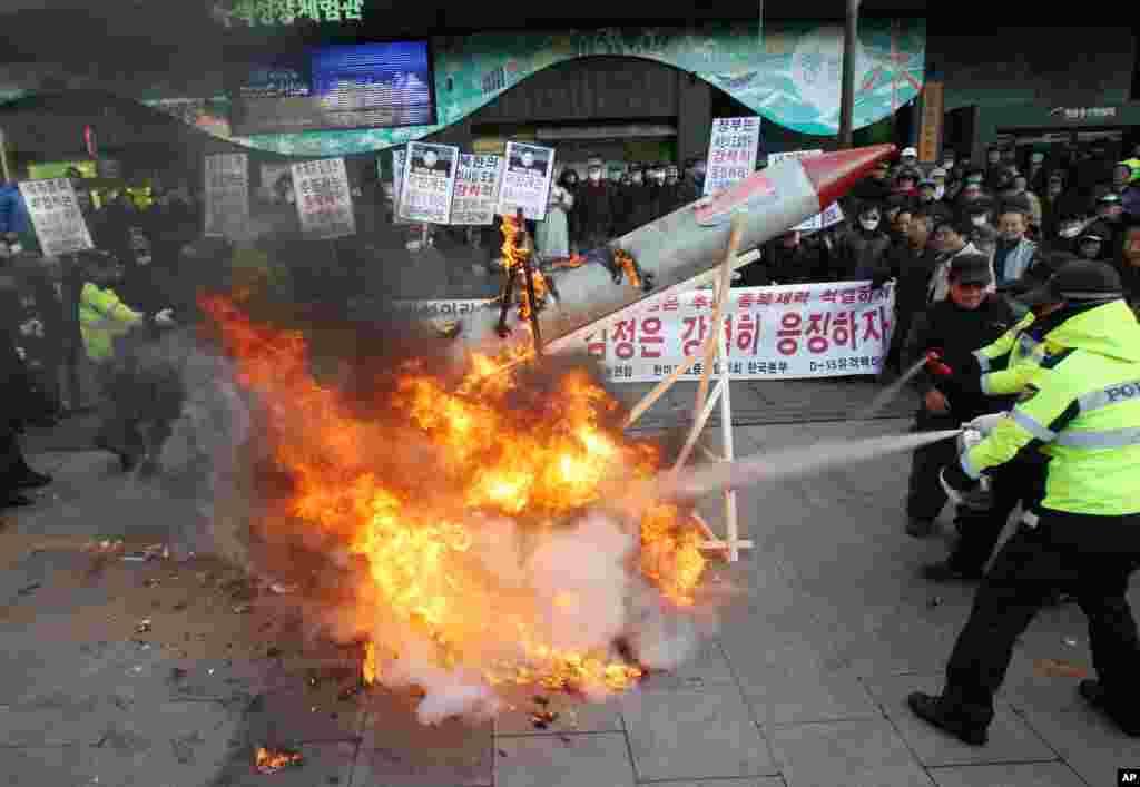 12일 한국 서울에서 북한 로켓 발사 규탄하며 모형 로켓을 불 태운 시위대. 경찰이 소화기를 동원해 불을 끄고 있다.