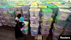 Polling clerks record information on a pile of ballot boxes containing cast ballot papers at the Chandaria tallying center in Kenya's coastal city of Mombasa, March 6, 2013.