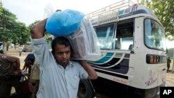 Seorang petugas pemilu Sri Lanka mengangkat kotak suara yang masih tersegel dari sebuah bus di pusat penghitungan suara di Jaffna, Sri Lanka (21/9).