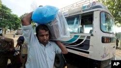 2013年9月21日,在斯里蘭卡北部城市賈夫納的一處計票中心,一名投票站工作人員把密封的票箱卸下巴士。泰米爾族選民就組建第一個能夠發揮功能的省政府進行了投票。