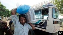 2013年9月21日,在斯里兰卡北部城市贾夫纳的一处计票中心,一名投票站工作人员把密封的票箱卸下巴士。泰米尔族选民就组建第一个能够发挥功能的省政府进行了投票。