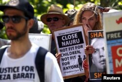 FILE - Protesters react as they hold placards and listen to speakers during a rally in support of refugees in central Sydney, Australia, Oct. 19, 2015.