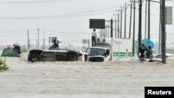 Người dân đứng lên mui xe để chờ cứu hộ khi sông Kinugawa tràn bờ vào thành phố Joso, Nhật Bản, ngày 10/9/2015.