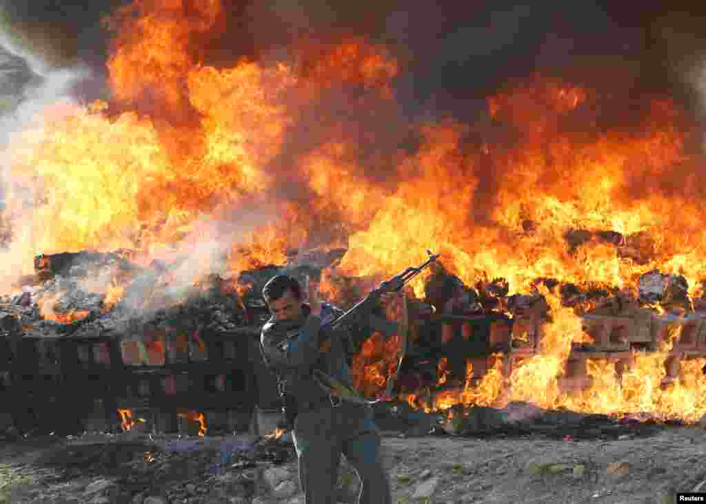 An Afghan officer reacts in front of a burning pile of seized narcotics and alcoholic drinks, in the outskirts of Kabul.