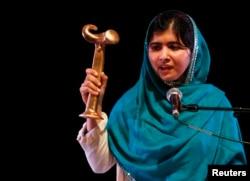Pakistan's Malala Yousafzai waves her RAW (Reach All Women) in War Anna Politkovskaya Award while giving a speech at the Southbank Center in London, Oct. 4, 2013.