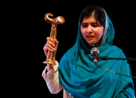 Pakistan's Malala Yousafzai waves her RAW (Reach All Women) in War Anna Politkovskaya Award while giving a speech at the Southbank Center in London, Oct. 4, 2013.
