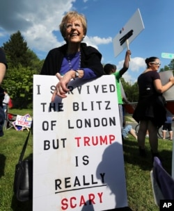 FILE - A voter holds a sign as she stands with others outside an event where Republican presidential candidate, Donald Trump and New Jersey Gov. Chris Christie were to appear on May 19, 2016 in Lawrenceville, N.J.