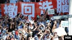 參與香港729反洗腦國民教育遊行的人士,以交叉手勢表達反對推行國民教育(美國之音湯惠芸)