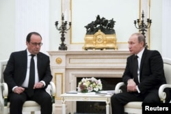 FILE - Russia's President Vladimir Putin, right, meets with French President Francois Hollande at the Kremlin in Moscow, Russia, Nov. 26, 2015. The leaders discussed coordinating efforts to combat Islamic State militants.