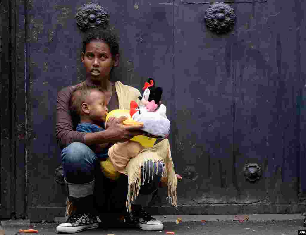 "A mother holds her child outside ""Baobab"" migration center next to the Tiburtina train station in Rome, Italy."