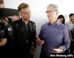 Apple CEO Tim Cook, right, looks at the new iPhone 6s with the members of OneRepublic, in the demo room after Apple event at the Bill Graham Civic Auditorium in San Francisco, Wednesday, Sept. 9, 2015.