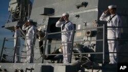 Navy sailors aboard the USS Halsey salute the USS Utah Memorial in Honolulu, Dec. 7, 2016.