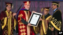 Afghan President Hamid Karzai receives an honorary degree from his Indian counterpart Pranab Mukherjee, second right, at the Lovely Professional University in Jalandhar, India, May 20, 2013.
