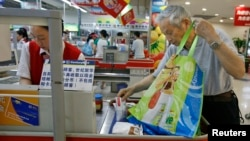 A shopper puts groceries he bought in his own bag after stores in China stopped giving free plastic bags at a supermarket in Beijing, June 1, 2008.