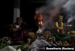 Dukun Tengger berdoa selama Festival Kasada di Gunung Bromo di Probolinggo, provinsi Jawa Timur Indonesia, 1 Agustus 2015. Penduduk desa dan jemaah melemparkan sesajen seperti ternak dan tanaman lainnya ke dalam kawah gunung berapi Gunung Bromo untuk bers