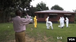 Health workers clean up after removing the body of an Ebola victim.