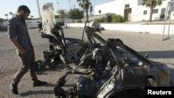 Seorang personil militer mengamati salah satu kendaraan yang meledak dekat Akademi Kepolisian Wanita di Tripoli, Minggu (19/8).
