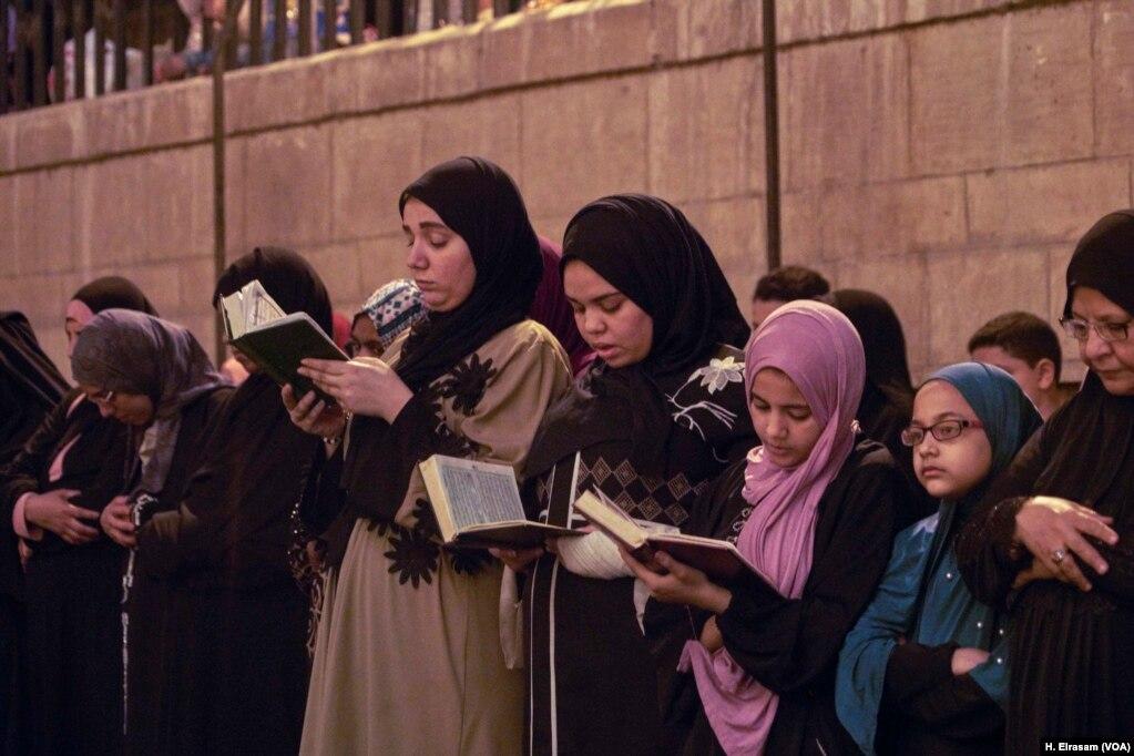 Мусульмане посещают молитвы, а некоторые следуют за чтением имама в своих Коранах в мечети Амр ибн аль-Ас, в Старом Каире, Египет, 31 мая 2019 года.