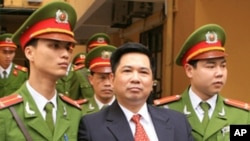 Cu Huy Ha Vu is escorted by policemen after his trial at a court in Hanoi, April 4, 2011. Vu, a legal scholar who sued Vietnam's prime minister and called for an end to one-party rule, was sentenced on Monday to seven years in prison.