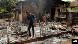 Seorang pria Muslim Sri Lanka memeriksa sisa-sisa tas menjahit yang hangus terbakar, pasca serangan kelompok garis keras Buddha Bodu Bala Sena di Aluthgama, 50 kilometer selatan Kolombo, Sri Lanka, Senin (16/6).