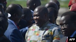 FILE - South Sudan rebel leader and former first vice president Riek Machar (C) is seen with supporters at Juba international airport, April 26, 2016. Having received medical treatment in the DRC, he is now in the Sudanese capital, Khartoum.