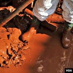 Pekerja di Hongaria membersihkan rumah dari lumpur beracun yang tumpah dari sebuah pabrik almunium di Hongaria.