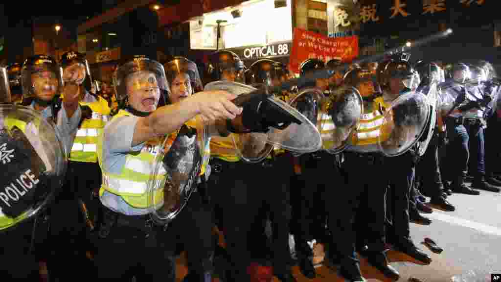 Riot police officers advance on a pro-democracy protest encampment in the Mong Kok district of Hong Kong, Oct. 19, 2014.