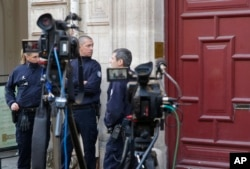 FILE - French police officers stand outside the residence of Kim Kardashian West in Paris, Oct. 3, 2016, after she was robbed at gunpoint Sunday..