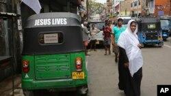 29일 스리랑카 콜롬보에서 히잡을 쓴 무슬림 여성이 도로를 건너고 있다.
