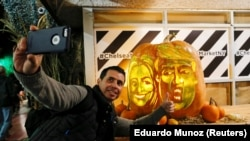 A man takes a selfie next to a giant pumpkin created by Master Carver Hugh McMahon with the faces of 2016 Democratic nominee Hillary Clinton and Republican presidential nominee Donald Trump at Chelsea Market in New York, U.S., October 28, 2016.