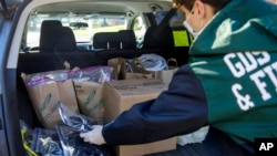 High school junior, Will Olsen, 17, of Kensington, Md., places bags holding pieces for medical face shields that were printed using personal 3D printers, into his car in Kensington, Md., Sunday, April 19, 2020. He then delivered the bags to the Eaton Hote