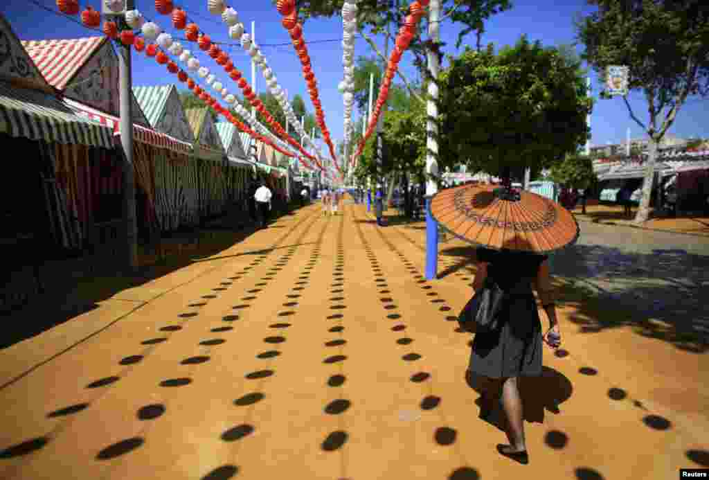 A woman holds an umbrella as she walks during the traditional Feria de Abril (April fair) in the Andalusian capital of Seville, southern Spain.