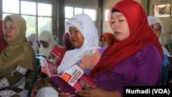 Sosialisasi pemberantasan perdagangan perempuan oleh Mitra Wacana di Yogyakarta, sekaligus pembagian buku saku Aman Merantau ke Luar Negeri, Yogyakarta, 9 Maret 2015 (Foto: VOA/Nurhadi)