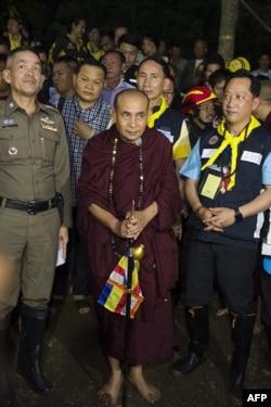 Budistički monah Kruba Bunčum, u centru, izlazi nakon zajedničke molitve sa rodbinom nestalih dečaka u Tam Luang pećini tokom akcije spasavanja, 4. jula 2018.